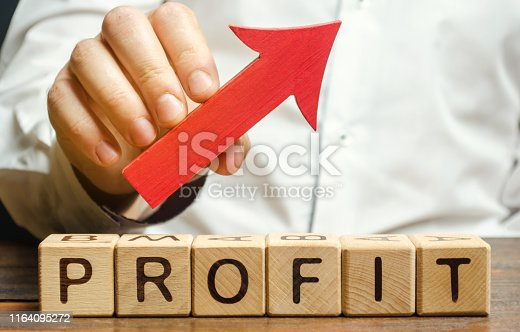 Wooden blocks with the word Profit and an up arrow. Concept of business success, financial growth and wealth. Increase profits and investment fund. Performance. Profitable business. ROR, ROI