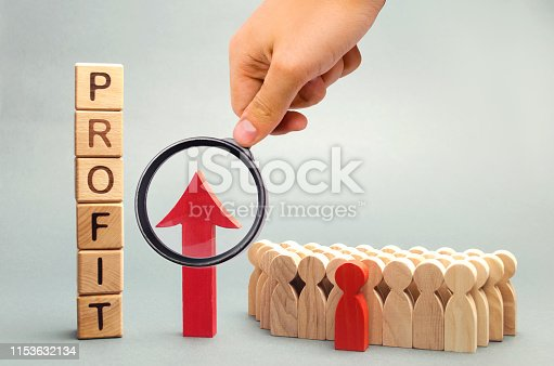875531516istockphoto Wooden blocks with the word profit and the graph up stands near the team. Concept of business success, financial growth and wealth. Increase profits and investment fund. Economic boom High performance 1153632134