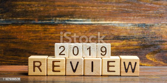 1186985932 istock photo Wooden blocks with the word Review 2019. Business concept. Feedback, Progress. New trends and prospects. Financial performance indicator. Results of the year. Financial and economic activities. Audit. 1162936528