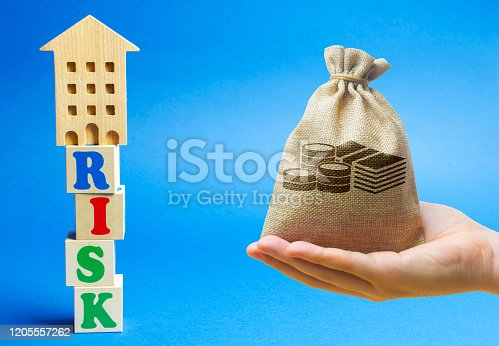 922107104istockphoto Wooden blocks with the word Risk and a miniature house with money bag. Real estate investment risks. Risky investments. Loss of property for non-payment. Debts. Mortgage tax. 1205557262