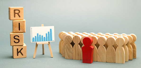 1163501702 istock photo Wooden blocks with the word Risk and a team with a leader. Business concept of teamwork, crisis solution and problem management. Business planning. Investment in the project. Risk assessment. Forecast 1132572834