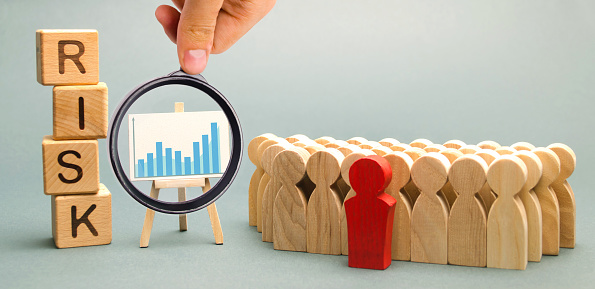 1163501702 istock photo Wooden blocks with the word Risk and a team with a leader. Business concept of teamwork, crisis solution and problem management. Business planning. Investment in the project. Risk assessment. Forecast 1152830692
