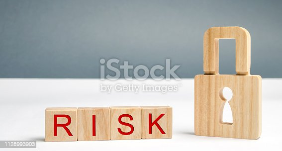 488497362istockphoto Wooden blocks with the word Risk and lock. Imperfect security system. High risk of hacking and theft of personal data. Insecure passwords. Risky investment. Suspicious Security Certificates 1128993903