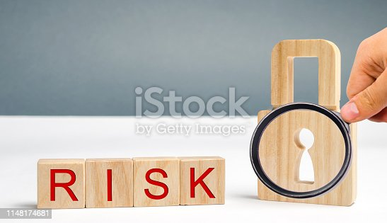 488497362istockphoto Wooden blocks with the word Risk and lock. Imperfect security system. High risk of hacking and theft of personal data. Insecure passwords. Risky investment. Suspicious Security Certificates 1148174681