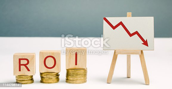 istock Wooden blocks with the word ROI and a poster with an arrow down. Financial ratio illustrating the level of business loss. Return on investment. Recession. Lower profitability and performance 1144298141