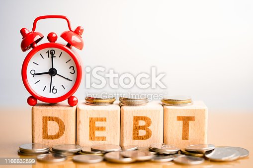 1024130248 istock photo Wooden blocks with word DEBT and coins stack. 1166632899