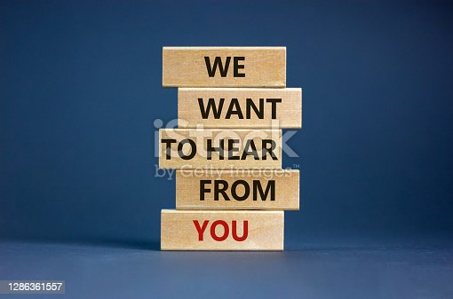 Wooden blocks with words 'we want to hear from you'. Beautiful grey background. Copy space. Business concept.