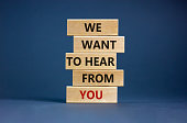 istock Wooden blocks with words 'we want to hear from you'. Beautiful grey background. Copy space. Business concept. 1286361557
