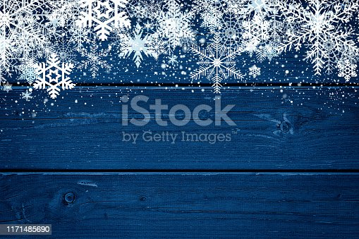Christmas and winter background with white snowflakes above a wood surface. Color treatment made with Photoshop.