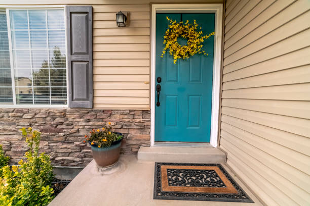 Wooden blue entrance door with floral wreath stock photo