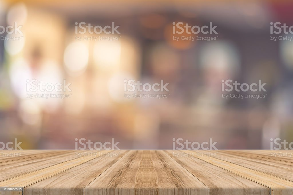 Wooden board empty table blur in coffee shop.