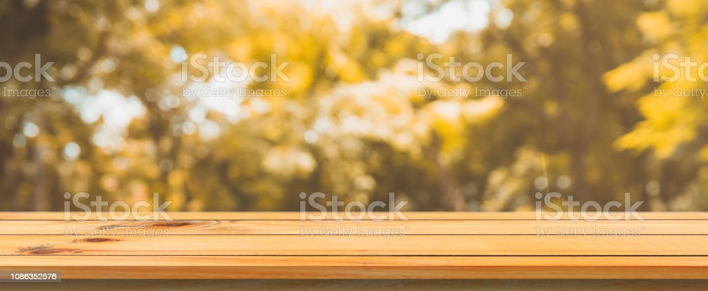 Wooden board empty table blurred background. Perspective brown wood...