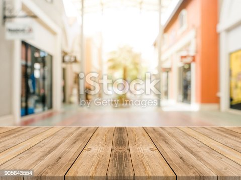 istock Wooden board empty table blurred shopping mall background. Perspective brown wooden table blur in department store background - can be used for display or montage your products. Mock up for of product 905643554