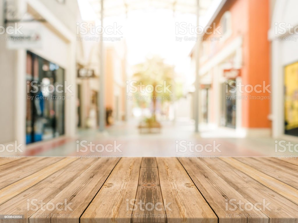 Wooden board empty table blurred shopping mall background. Perspective brown wooden table blur in department store background - can be used for display or montage your products. Mock up for of product stock photo