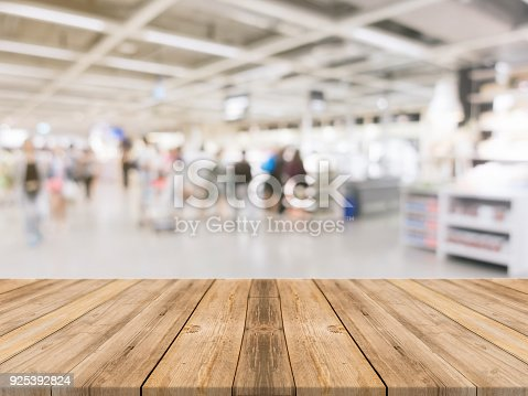 istock Wooden board empty table blurred shopping mall background. Perspective brown wooden table blur in department store background - can be used for display or montage your products. Mock up for of product 925392824