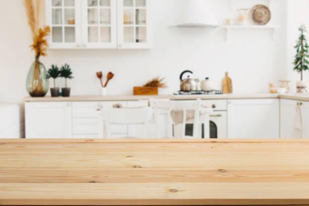 drewniana deska pusty stół przed rozmytym tle. perspektywa brązowe drewno z rozmytym tle kuchni i wyposażenia kuchni - może być używany do wykazania lub montażu produktów. - kuchnia zdjęcia i obrazy z banku zdjęć