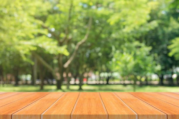holzbrett leere tabelle vor unscharfen hintergrund. perspektive braun holztisch über unschärfe bäume im wald hintergrund - kann verwendet werden für die anzeige zu verspotten oder montage ihrer produkte. frühjahrssaison. - vorschuldekorationen stock-fotos und bilder