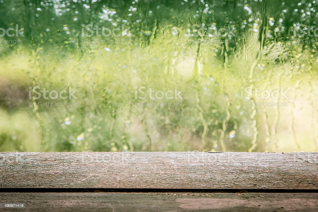 Wooden board empty table in front of blurred rainy window background....
