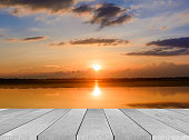 istock wooden board empty table sea and sky sunset background 584483188