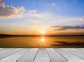 istock wooden board empty table sea and sky sunset background 584483272