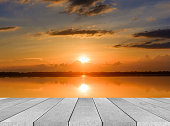 istock wooden board empty table sea and sky sunset background 584483346