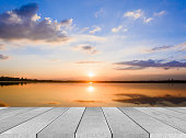 istock wooden board empty table sea and sky sunset background 584483424