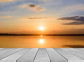 istock wooden board empty table sea and sky sunset background 584483496