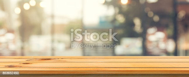 istock Wooden board empty table top blurred background. Perspective brown wood table over blur in coffee shop background. Panoramic banner - can be used mock up for montage products display or design. 853652450