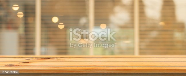 istock Wooden board empty table top blurred background. Perspective brown wood table over blur in coffee shop background. Panoramic banner - can be used mock up for montage products display or design. 874189962