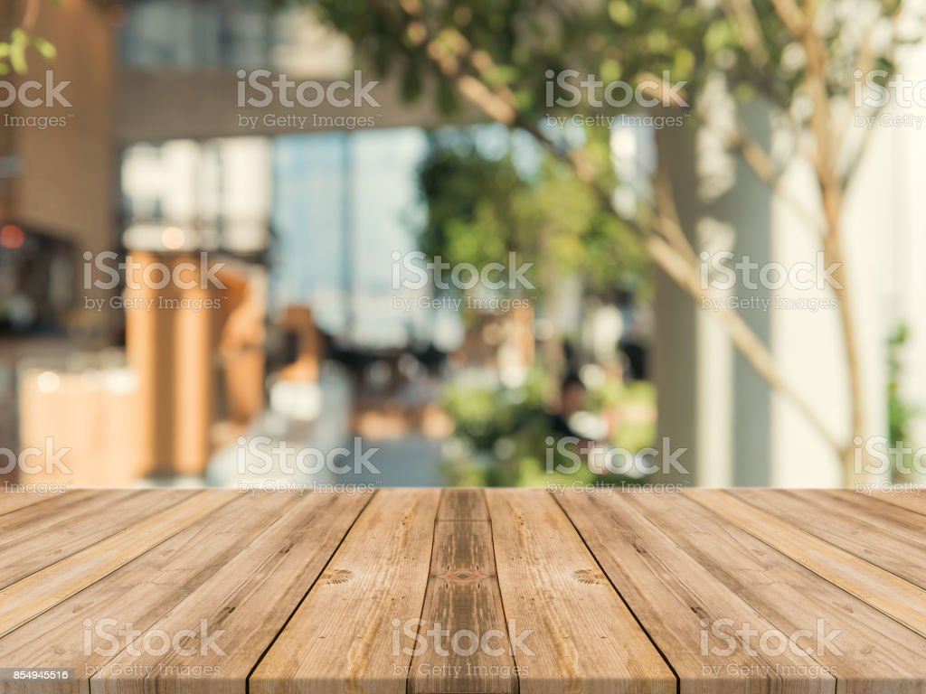 Wooden board empty table top on of blurred background. Perspective brown wood table over blur in coffee shop background - can be used mock up for montage products display or design key visual layout. stock photo