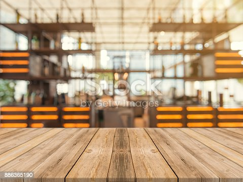 istock Wooden board empty table top on of blurred background. Perspective brown wood table over blur in coffee shop background - can be used mock up for montage products display or design key visual layout. 886365190