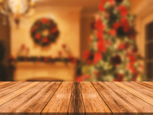 wooden board empty table top on of blurred background. perspective brown wood table over blur christmas tree and fireplace background, can be used mock up for montage products display or design layout - christmas table imagens e fotografias de stock