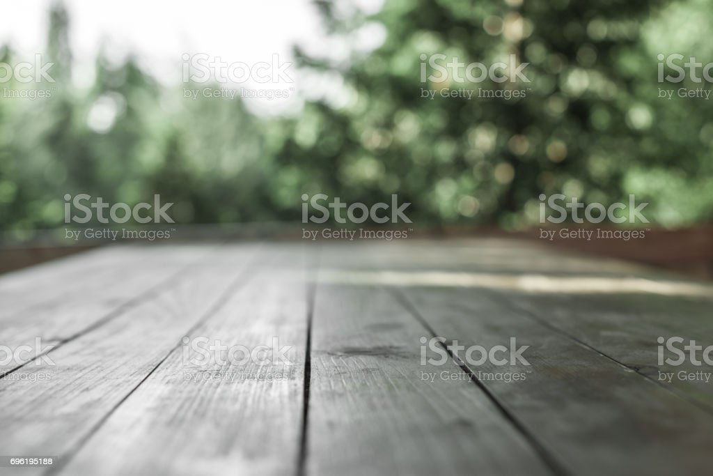 Wooden board  in front of blurred nature background. stock photo