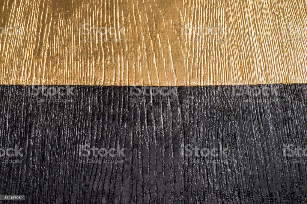 Holzbrett in schwarz und gold lackiert – Foto