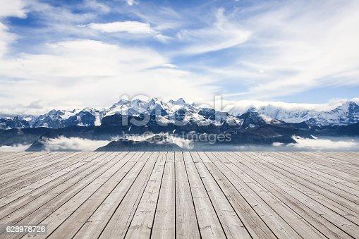 istock Wooden board towards snowcapped mountain 628978726