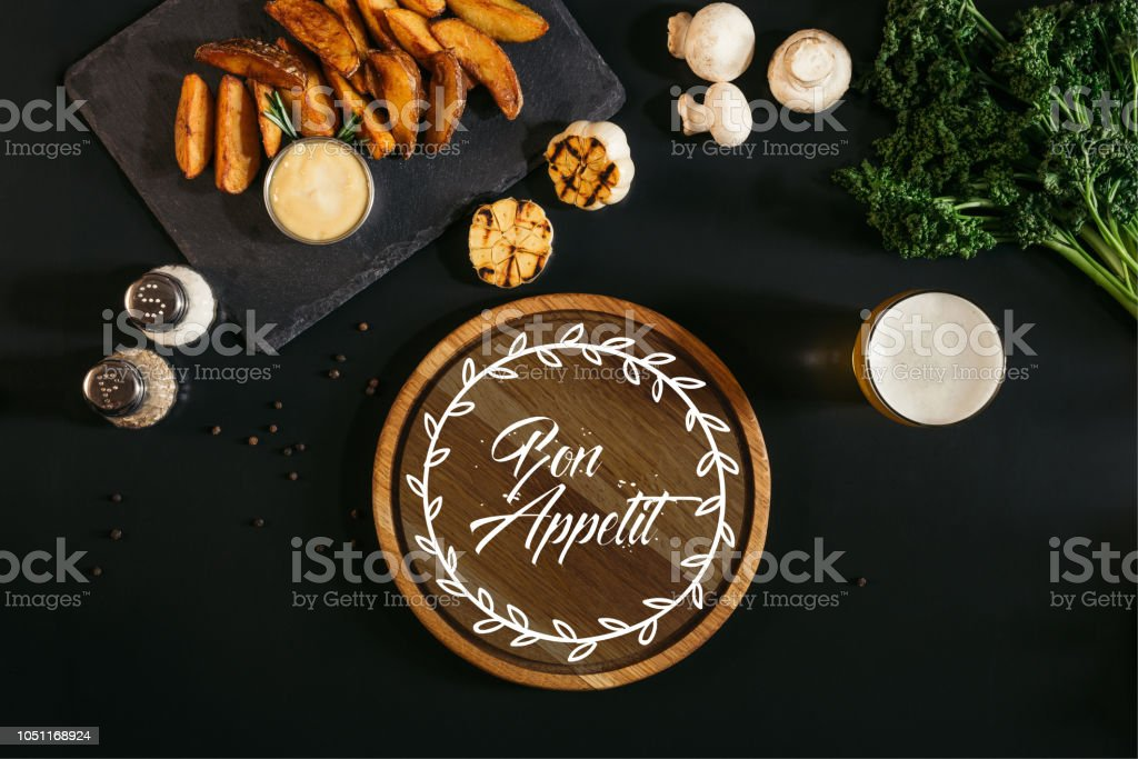 wooden board with 'bon appetit' lettering, glass of beer and baked potatoes with sauce and spices on black stock photo