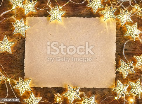istock Wooden board with card and garland 636658632