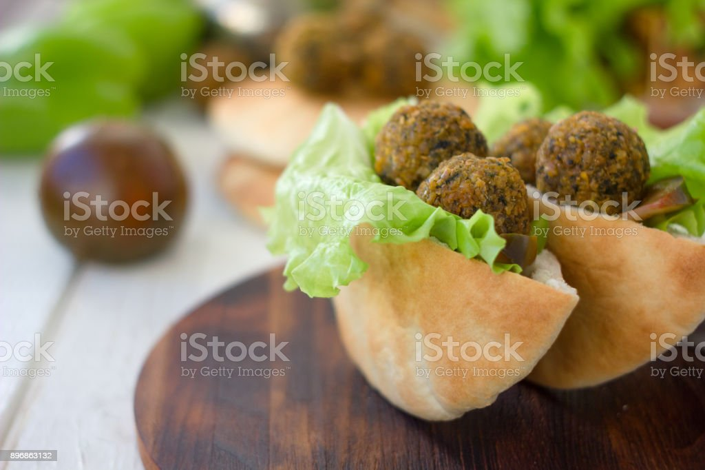 Wooden board with falafel in pita inside. stock photo