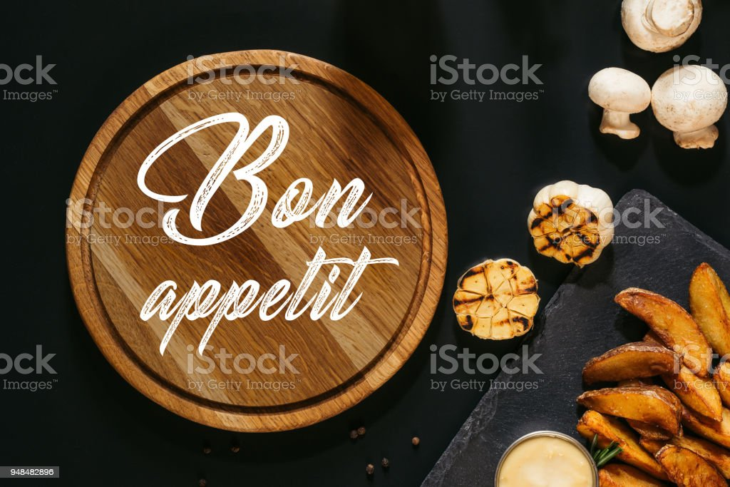 wooden board with inscription bon appetit, grilled garlic, mushrooms and baked potatoes with sauce on black stock photo