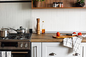 wooden board with knife, tomatoes, olive oil on modern kitchen countertop and steel stove with saucepan. cooking food. Stylish gray kitchen interior design in scandinavian style