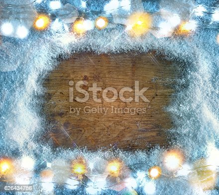 636659848 istock photo Wooden board with snowflakes and garland. Top View. 626434786