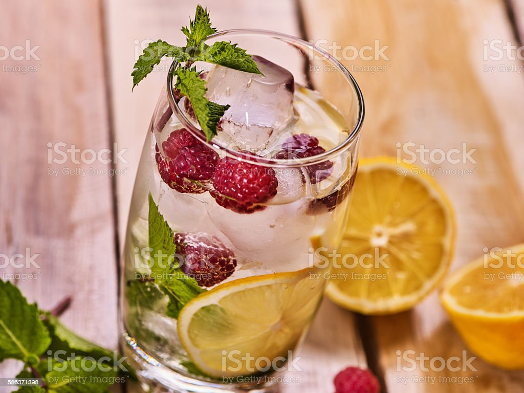 Wooden boards is glasses with raspberry mojito and cubes ice. stock photo