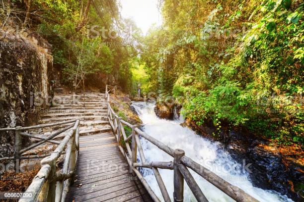 Photo of Wooden boardwalk and stone stairs leading along mountain river