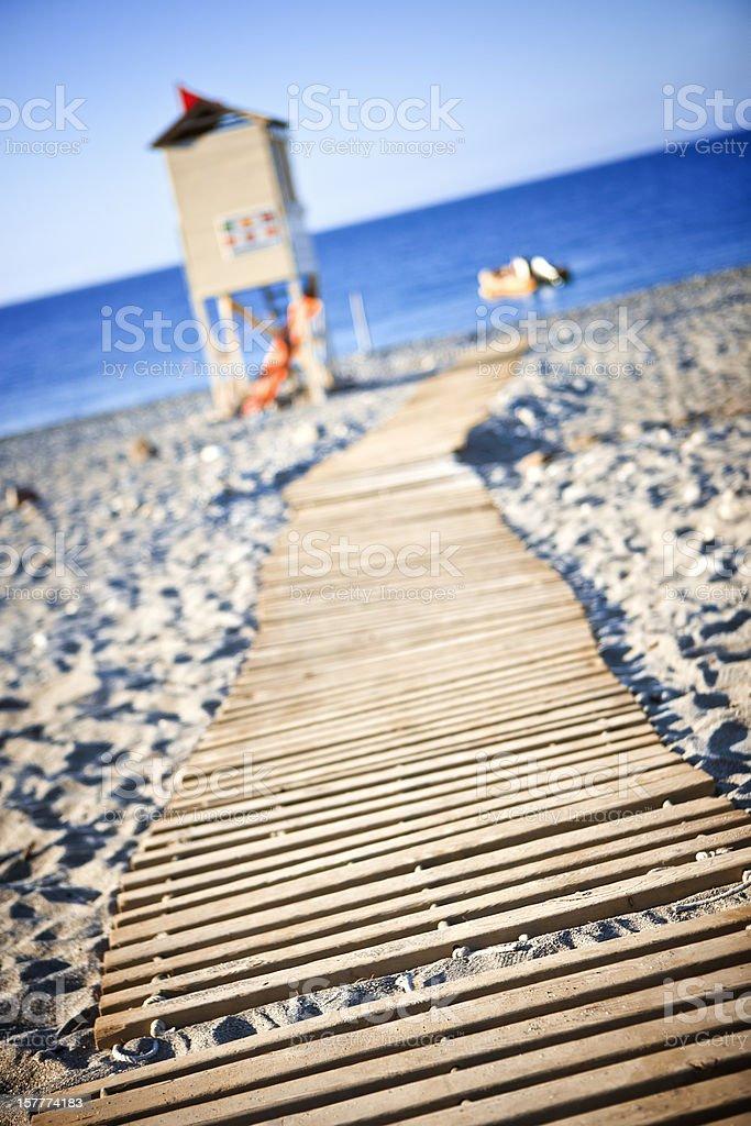 Wooden boardwalk towards beach stock photo