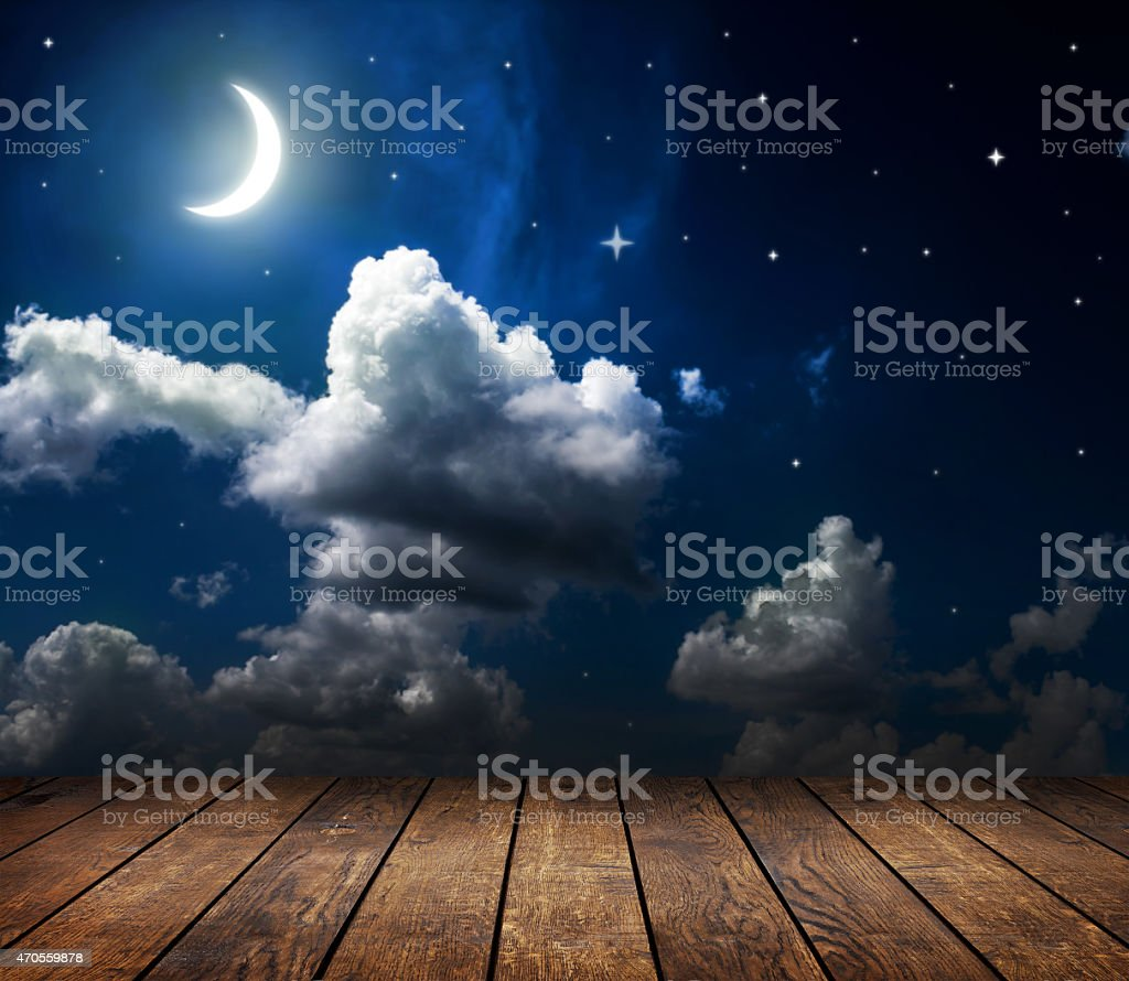 Wooden boardwalk under the moon and stars stock photo