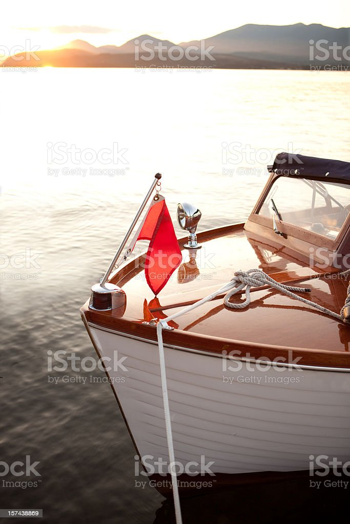 Wooden boat at anchor during sunset stock photo