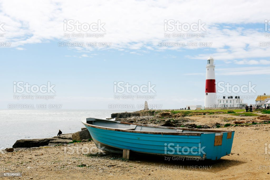 Wooden boat by the seaside and Portland Bill Lighthouse on the Isle of Portland, UK stock photo