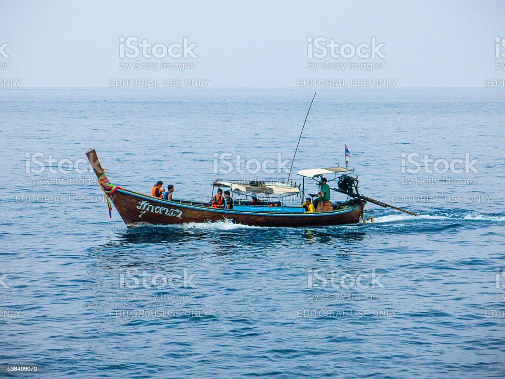 Wooden Boat containing several Men and Women stock photo