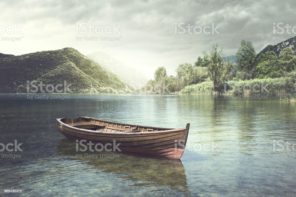 Wooden boat floating in a mystic river stock photo