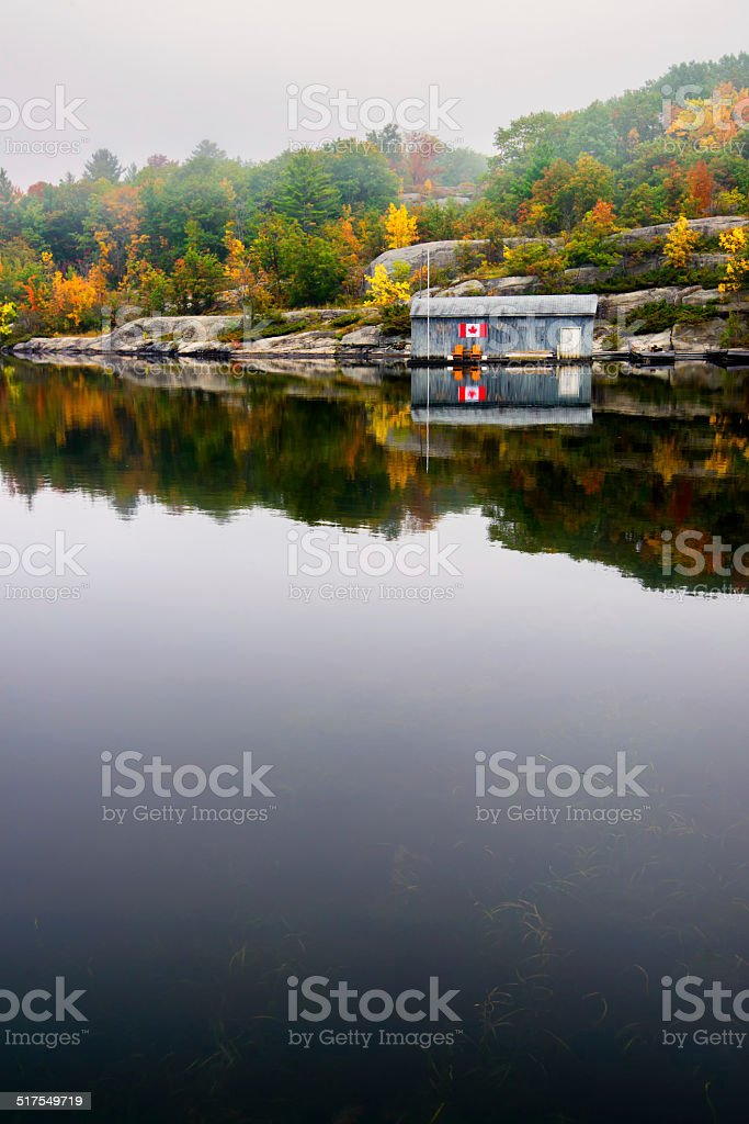 Wooden Boat House on a Calm Lake in the Fall stock photo